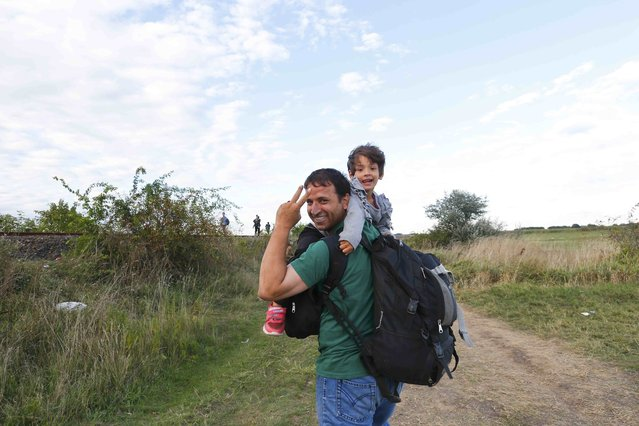 A migrant carries his child as they arrive to a collection point in the village of Roszke, Hungary, September 6, 2015, after crossing the border from Serbia. (Photo by Laszlo Balogh/Reuters)