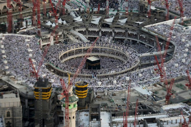 An aerial view shows Muslim worshippers praying at the Grand mosque surrounded by construction cranes, in the holy city of Mecca in this July 14, 2015 file photo. At least 65 people were killed when a crane crashed in Mecca's Grand Mosque on September 11, 2015, Saudi Arabia's Civil Defence authority said, in an accident that came just weeks before Islam's annual haj pilgrimage. (Photo by Ali Al Qarni/Reuters)