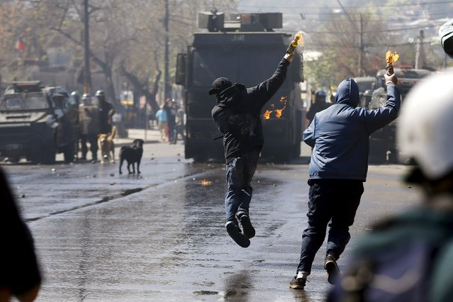 Demonstrators throw  Molotov cocktails against riot policemen during a protest marking the country's 1973 military coup, in Santiago, Chile September 13, 2015. (Photo by Ivan Alvarado/Reuters)