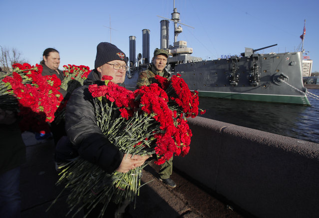 Communists carry flowers to put on embankment at the Aurora Cruiser during the celebration of the 100th anniversary of the 1917 Bolshevik revolution in St.Petersburg, Russia, Tuesday, November 7, 2017. (Photo by Dmitri Lovetsky/AP Photo)