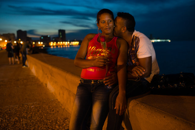 As the sun sets on the Malecon in Havana on Friday January 23, 2015, Yurania Fabie, 31, left, is embraced by her boyfriend, Eduardo Fromata, 25. (Photo by Sarah L. Voisin/The Washington Post)