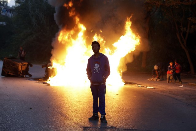 A young Roma man stands next to a burning barricade during a protest in Athens on Tuesday, September 30, 2014. The Greek Roma community, protesting authorities' plans to demolish their illegal settlement and move them to a remote spot in the countryside, blocked a main northern Athens avenue for hours Tuesday, using rubbish bins that they then set on fire.  (Photo by Thanassis Stavrakis/AP Photo)