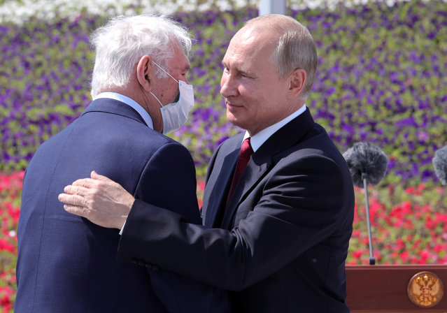 Russian President Vladimir Putin, right, congratulates the president of the Scientific Research Institute for Emergency Children's Surgery and Traumatology Leonid Roshal during a ceremony of handing Gold Stars medals to heroes of labor marking the Day of Russia holiday in Moscow, Russia, on Friday, June 12, 2020. The ceremony marked the first big public event Putin attended since announcing a nationwide lockdown more than two months ago. (Photo by Mikhail Klimentyev/Sputnik/Kremlin Pool Photo via AP Photo)