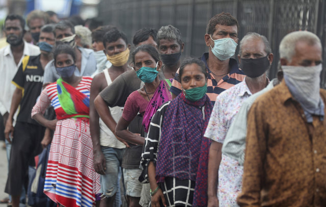Homeless people wearing masks stand in a queue to receive food being distributed in Mumbai, India, Saturday, June 20, 2020. India is the fourth hardest-hit country by the COVID-19 pandemic in the world after the U.S., Russia and Brazil. (Photo by Rafiq Maqbool/AP Photo)