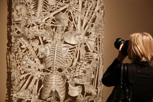 A visitor to the Death: A Self-portrait exhibition at the Wellcome Collection takes a photograph of Hungarian artist Balint Zsalko's collage entitled Monolith on November 14, 2012 in London, England. The exhibition showcases 300 works from a unique collection by Richard Harris, a former antique print dealer from Chicago, devoted to the iconography of death. The display highlights art works, historical artifacts, anatomical illustrations and ephemera from around the world and opens on November 15, 2012 until February 24, 2013.  (Photo by Peter Macdiarmid)
