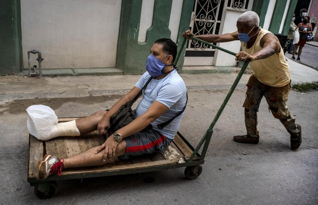 A man with his leg in a cast and wearing a protective face mask as a precaution against the spread of the coronavirus, is transported on a dolly, in Havana, Cuba, Wednesday, May 13, 2020. Cuban authorities are requiring the use of masks for anyone outside their homes amid the COVID-19 pandemic. (Photo by Ramon Espinosa/AP Photo)