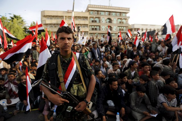 A Houthi militant stands guard as people watch a ceremony marking the first anniversary of the Houthi movement's takeover of Yemen's capital Sanaa September 21, 2015. (Photo by Khaled Abdullah/Reuters)