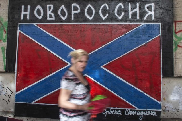A woman walks past a graffiti depicting a flag of Novorossiya (New Russia) in Belgrade, Serbia, October 11, 2014. On Thursday, guns, tanks and planes will be back in Belgrade, now capital of Serbia, for a Liberation Day parade held four days early to accommodate the guest of honour – Russian President Vladimir Putin, en route to a summit in Milan. (Photo by Marko Djurica/Reuters)