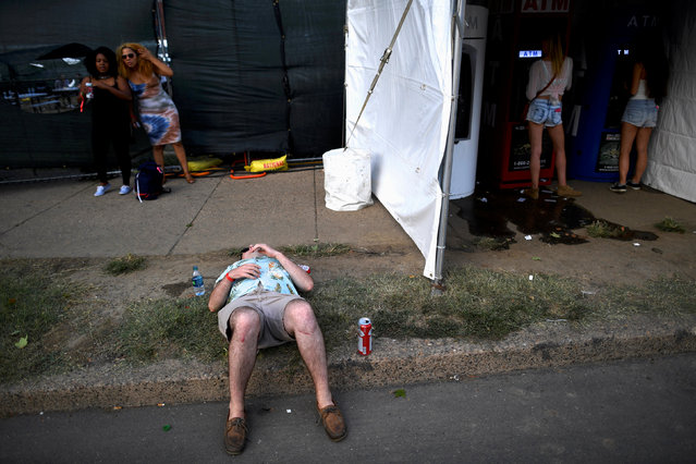 A man sleeps while women withdraw money during the fifth annual Made in America Music Festival in Philadelphia, Pennsylvania September 3, 2016. (Photo by Mark Makela/Reuters)