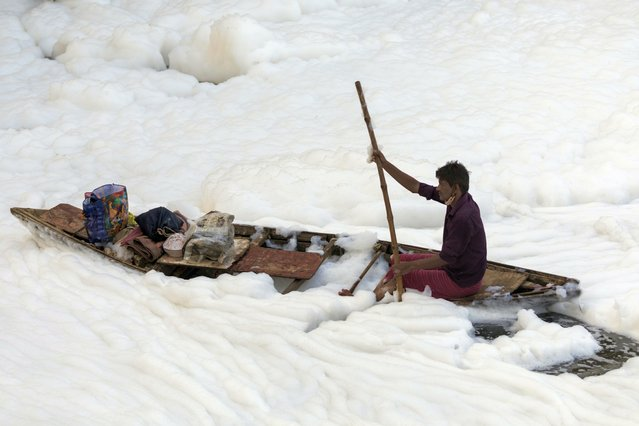 A man rows his boat amidst foam in the polluted Yamuna river on the outskirts of New Delhi on July 23, 2020. (Photo by Xavier Galiana/AFP Photo)