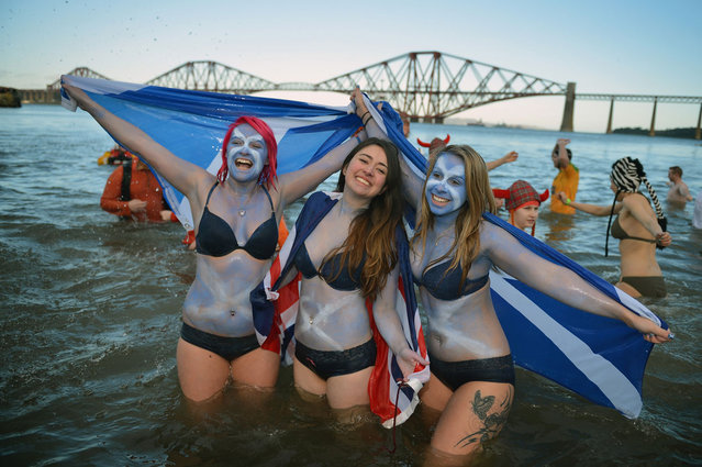 Girls holding saltire flags join around a thousand New Year swimmers, many in costume, who braved freezing conditions in the River Forth in front of the Forth Rail Bridge during the annual Loony Dook Swim on January 1, 2013 in South Queensferry, Scotland. Thousands of people gathered last night to see in the New Year at Hogmanay celebrations in towns and cities across Scotland.  (Photo by Jeff J. Mitchell)