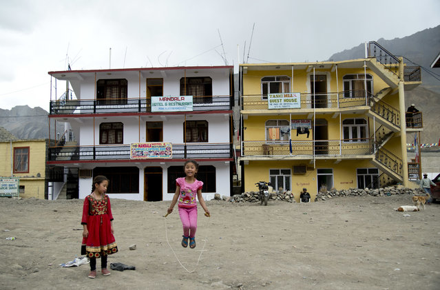 In this August 20, 2016, photo, two girls play in front of newly constructed hotels in Kaza, headquarters of the Spiti Valley, India. (Photo by Thomas Cytrynowicz/AP Photo)