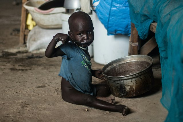 A child eats porridge sitting on the floor of a shelter at Mangateen Internal Displaced persons (IDPs) center in Juba on November 17, 2018. Some 5000 IDPs have been relocated to a new resettlement centre from the UN Protection of Civilians site (POC) after ethnic clashes erupted in the POC. (Photo by Akuot Chol/AFP Photo)
