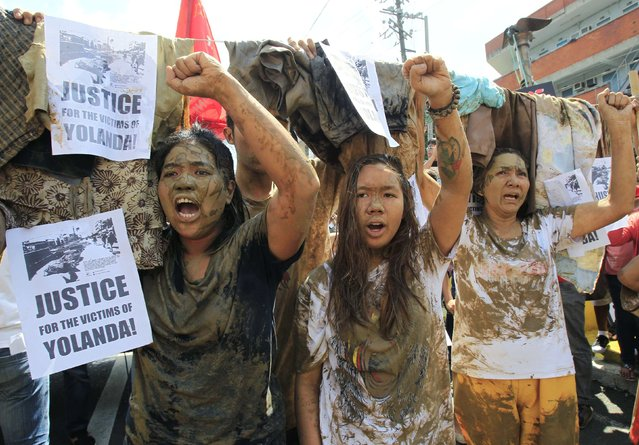 Protesters covered with mud shout anti-government slogans during a protest outside the presidential palace in Manila November 7, 2014, a day before the anniversary of Typhoon Haiyan that hit Tacloban city, central Philippines. The protest was held to demand justice for victims of Typhoon Haiyan, known in the Philippines as Typhoon Yolanda, which left more than 7,000 dead or missing last November 8. (Photo by Romeo Ranoco/Reuters)