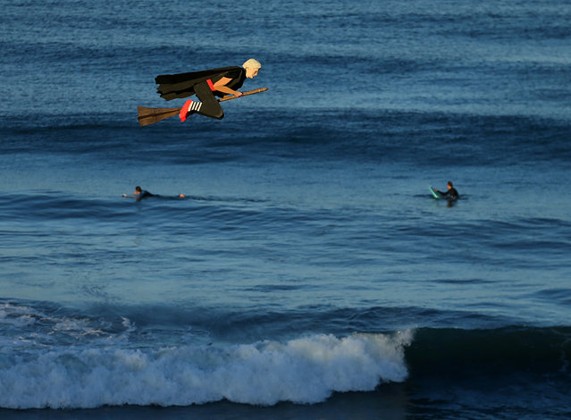 A remote control plane resembling U.S. Presidential candidate Hillary Clinton flies along the beach and past surfers in Carlsbad, California, U.S. September 15, 2016. (Photo by Mike Blake/Reuters)