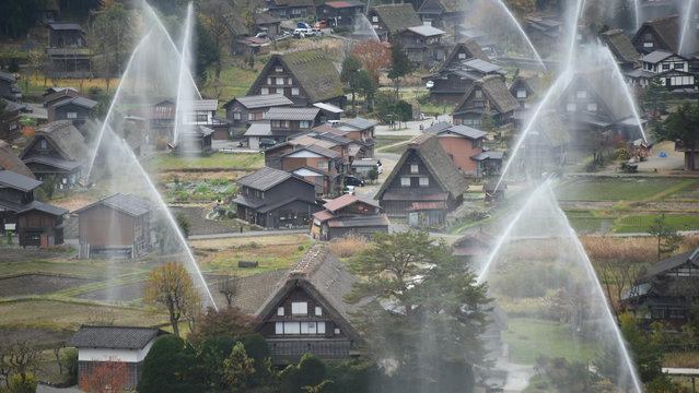 The frond house is Wada House, the biggest house at Shirakawa-go. Water is seen discharged over the traditional farm houses at Shirakawa-go, the UNESCO World Heritage site on November 9, 2014 in Shirakawa, Japan. This annual drill is held to prevent fire. (Photo by Kaz Photography/Getty Images)