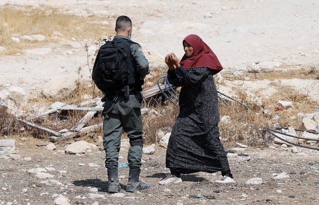 A Palestinian woman gestures towards Israeli border police guard as an Israeli bulldozer demolishes a house in the West Bank area of Masafer near Yatta, 02 September 2020. Israel on a regular basis demolishes Palestinians' houses in the West Bank citing missing building permits for Area. (Photo by Abed Al Hashlamoun/EPA/EFE)