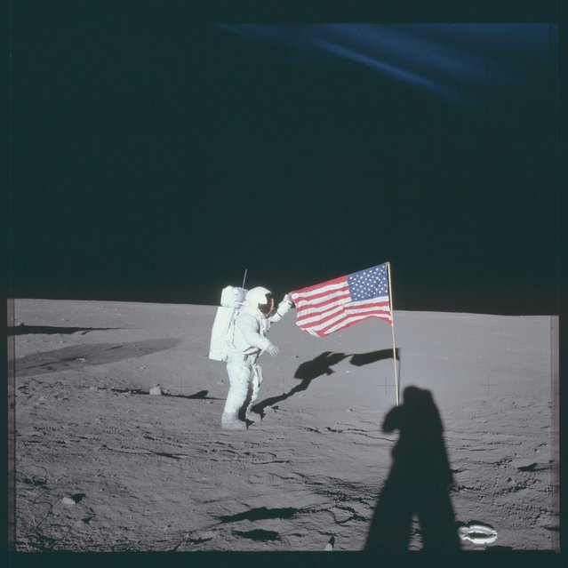 "Astronaut Charles ""Pete"" Conrad Jr., Apollo 12 commander, stands beside the United States flag on the lunar surface during the first extravehicular activity in this November 16, 1969 NASA handout photo. (Photo by Reuters/NASA)"