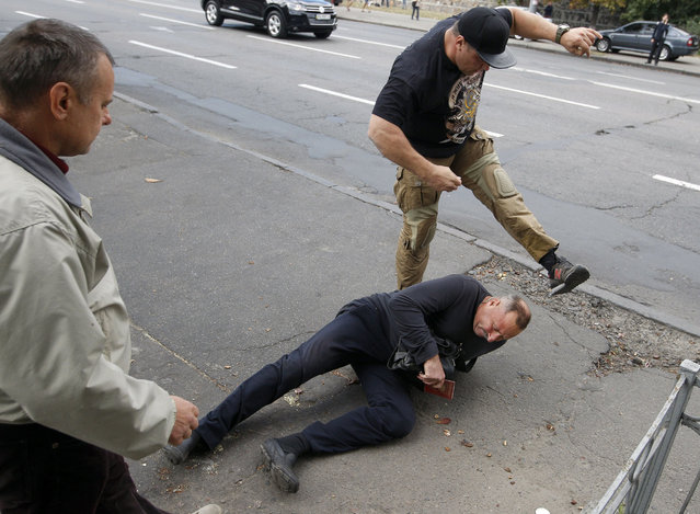 A Ukrainian protester (up) kicks a Russian man during protest in front of the Russian embassy in Kiev on September 18, 2016, where a polling station for Russia's parliamentary election was open. Russians went to the polls on September 18 in parliamentary elections, with parties loyal to President Vladimir Putin set to maintain their dominance despite the longest economic crisis of his rule. (Photo by Yuri Kirnichny/AFP Photo)