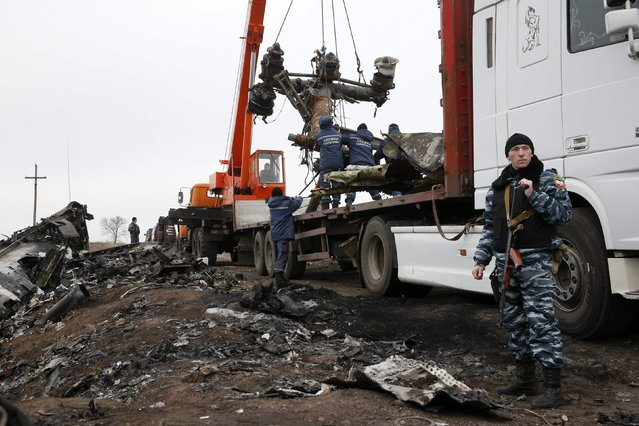 Local workers carry wreckage from the downed Malaysia Airlines flight MH17 at the site of the plane crash near the village of Hrabove (Grabovo) in Donetsk region, eastern Ukraine November 16, 2014. (Photo by Maxim Zmeyev/Reuters)