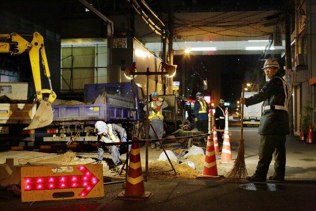 Men work at a construction site at night in Osaka, western Japan November 19, 2014. (Photo by Thomas Peter/Reuters)