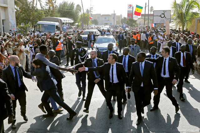 Members of security services react as a man in the crowd tries to shake hands with French President Emmanuel Macron (C), who walks next to Senegalese President Macky Sall in a street of Saint-Louis, Senegal, February 3, 2018. (Photo by Ludovic Marin/Reuters)