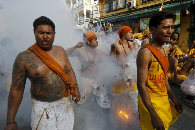 Devotees of the Chinese Ban Tha Rue shrine reacts as fire crackers explode during a procession celebrating the annual vegetarian festival in Phuket, Thailand, October 17, 2015. (Photo by Jorge Silva/Reuters)