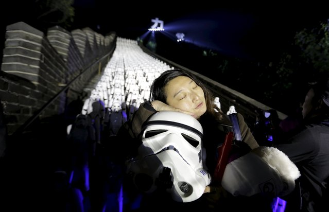 """A fan holding a Stormtrooper helmet from """"Star Wars"""" poses for a photo, in front of five hundred replicas of the Stormtrooper characters at the Juyongguan section of the Great Wall of China during a promotional event for """"Star Wars: The Force Awakens"""" film, on the outskirts of Beijing, China, October 20, 2015. (Photo by Jason Lee/Reuters)"""
