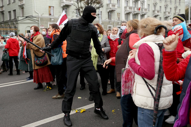 Belarusian pensioners argue with a law enforcement officer during a rally to demand the resignation of authoritarian leader and new fair election in Minsk on October 12, 2020. (Photo by AFP Photo/Stringer)