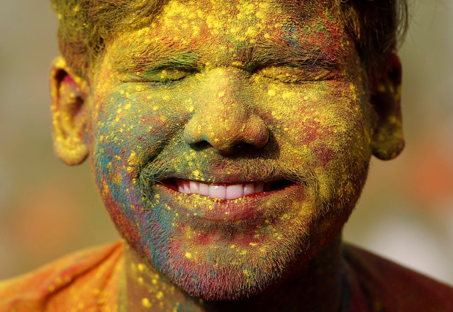 A student of Rabindra Bharati University, with his face smeared in coloured powder, reacts as his fellow student throws coloured powder on his face during Holi celebrations inside the university campus in Kolkata, India, February 26, 2018. (Photo by Rupak De Chowdhuri/Reuters)