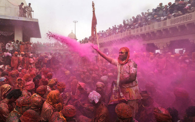 Indian Hindu devotees smeared with colors,sing at the Nandagram temple famous for Lord Krishna and his brother Balram, during Lathmar holy festival, in Nandgaon, India , Friday, March 22, 2013. During Lathmar Holi the women of Nandgaon, the hometown of Krishna, beat the men from Barsana, the legendary hometown of Radha, consort of Hindu God Krishna, with wooden sticks in response to their teasing as they depart the town. (Photo by Manish Swarup/AP Photo)