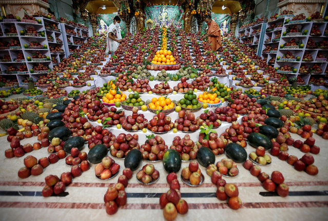 Priests arrange fruits kept inside a temple as offerings by Hindu devotees as part of a ritual to mark the Annakut festival in Ahmedabad, India, October 13, 2020. According to the priests, the fruits will be distributed among the coronavirus disease (COVID-19) affected believing it will cure them. (Photo by Amit Dave/Reuters)