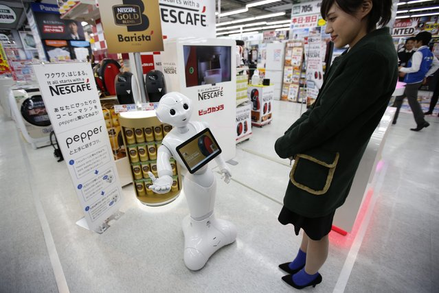 "SoftBank Corp's human-like robot named ""Pepper"" gestures as it introduces Nestle's coffee machines at an electric shop in Tokyo December 1, 2014. Nestle SA started to use robots to help sell its coffee makers at electronics stores across Japan, becoming the first corporate customer for the chatty, bug-eyed androids unveiled in June by tech conglomerate SoftBank Corp. (Photo by Issei Kato/Reuters)"