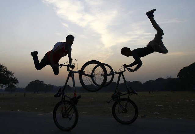 Cyclists perform a stunt as they practice ahead of the Hip-Hop Carnival in Kolkata December 2, 2014. The cyclists will perform in the carnival which  be will be held in Kolkata on December 13, the cyclists said. (Photo by Rupak De Chowdhuri/Reuters)