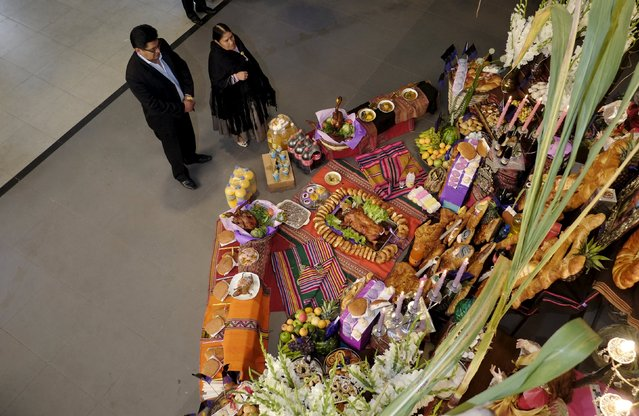 "Relatives of Genara Aguirre stand next to an offering in her honor during the ""All Saints Day"" celebrations in La Paz, Bolivia, November 1, 2015. (Photo by David Mercado/Reuters)"