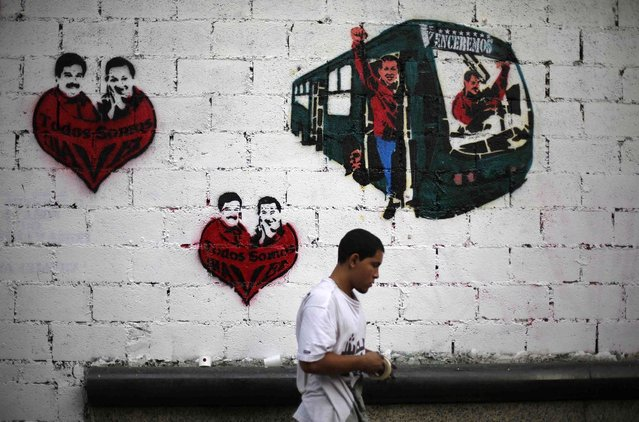 """A street artist stands in front of a wall with graffiti showing late Venezuela President Hugo Chavez and current acting President and presidential candidate Nicolas Maduro in Caracas April 10, 2013. Venezuelans will hold presidential elections on April 14. The graffiti (L and C) read, """"We are all Chavez"""". (Photo by Tomas Bravo/Reuters)"""