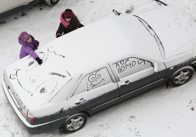 Children draw on a car covered in snow in a yard in Kiev December 7, 2014. (Photo by Gleb Garanich/Reuters)