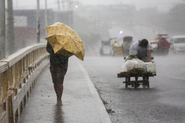 A woman uses an umbrella as she crosses a bridge under heavy rains brought by typhoon Vamco in Navotas City, Philippines on Thursday. November 12, 2020. (Photo by Basilio Sepe/AP Photo)