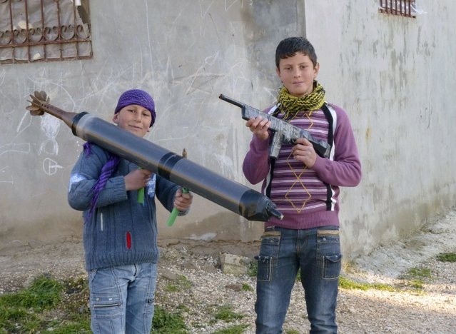 Boys hold up toy guns in the town of Hula near the city of Homs March 2, 2012. (Photo by Reuters)