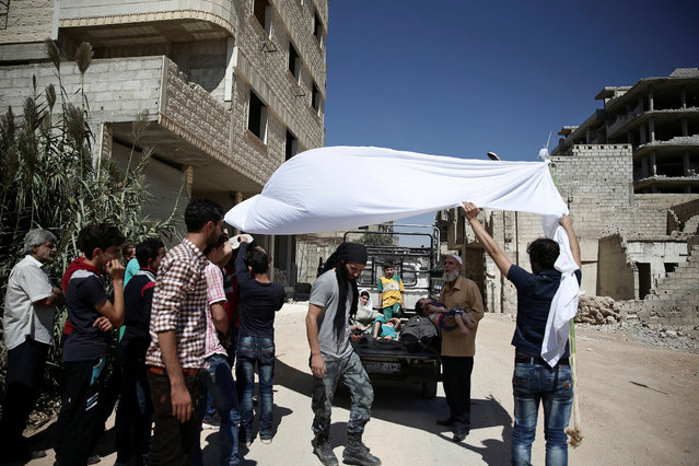 "Men hold a white cloth over actors as they perform a scene in a film directed by Humam Husari in the rebel-held besieged town of Zamalka, in the Damascus suburbs, Syria September 19, 2016. A Syrian filmmaker whose harrowing footage of sarin gas victims in 2013 was seen around the world is using his experience of the attack and conflict to make a drama looking at why people take up arms in a war which began as a peaceful revolution. Humam Husari's self-financed short film explores the chemical attack near Damascus through the eyes of a rebel fighter who lost his wife and child but was denied time to bury them. Instead, he is called to defend his town from a government offensive. The story is based on real-life events, he said. ""We need to understand how people were pushed into this war and to be part of it"", said Husari, 30. ""I am talking about a story that I lived with. They are real characters"". (Photo by Bassam Khabieh/Reuters)"