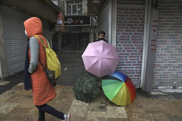 A vendor sells umbrellas outside closed shops in northern Tehran, Iran, Sunday, November 22, 2020. Iran on Saturday shuttered businesses and curtailed travel between its major cities, including the capital of Tehran, as it grapples with the worst outbreak of the coronavirus in the Mideast region. (Photo by Vahid Salemi/AP Photo)