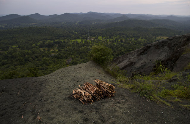 In this September 12, 2014 photo, bundles of wood collected and left behind on top of Roro hills sit on loose asbestos to be rolled downhill at the end of the day in Roro, India. (Photo by Saurabh Das/AP Photo)