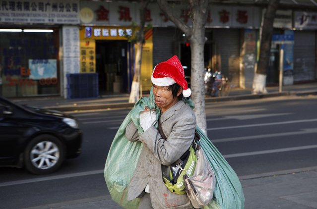 A man wearing a Santa hat carries giant bags as he walks along a street at an old area of Liwan district in Guangzhou, Guangdong province December 23, 2014. (Photo by Alex Lee/Reuters)