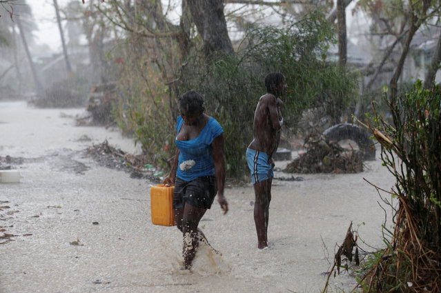 A woman carries a jug of water as she walks on a flooded street during rain after Hurricane Matthew in Les Cayes, Haiti, October 17, 2016. (Photo by Andres Martinez Casares/Reuters)