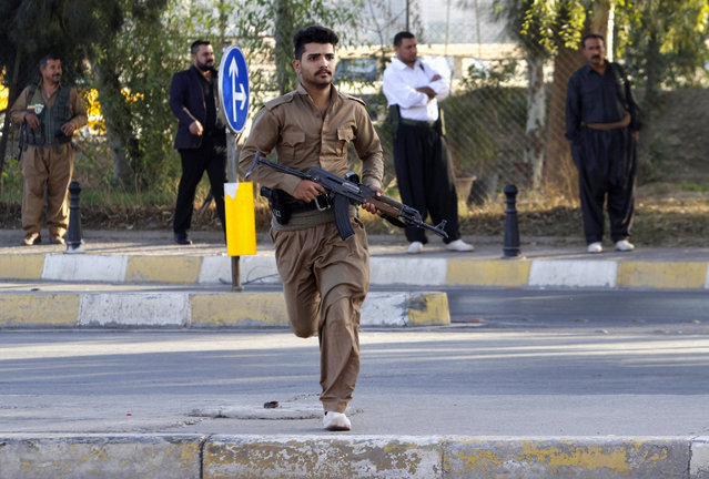 A member of peshmerga forces runs at a site of an attack by Islamic State militants in Kirkuk, Iraq, October 21, 2016. (Photo by Ako Rasheed/Reuters)