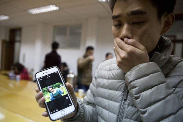 A man who only gave his surname Zhao shows a photo of his girlfriend Pan Haiqin who was killed in the deadly stampede in Shanghai, China, Friday, January 2, 2015. People unable to contact friends and relatives streamed into hospitals Thursday, anxious for information after a stampede during New Year's celebrations in Shanghai's historic waterfront area killed 36 people in the worst disaster to hit one of China's showcase cities in recent years. (Photo by Ng Han Guan/AP Photo)