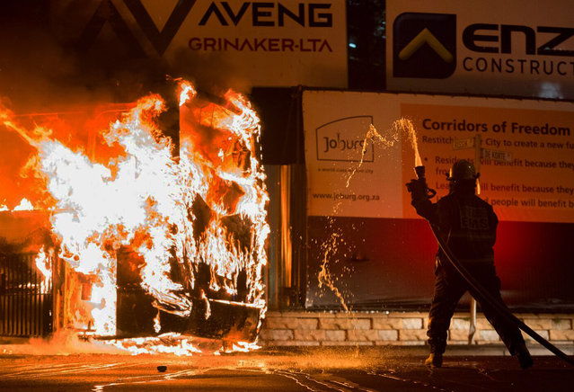 A fireman attempts to extinguish a burning bus in Braamfontein, Johannesburg, South Africa, Tuesday, October 25, 2016. (Photo by Yeshiel Panchia/AP Photo)