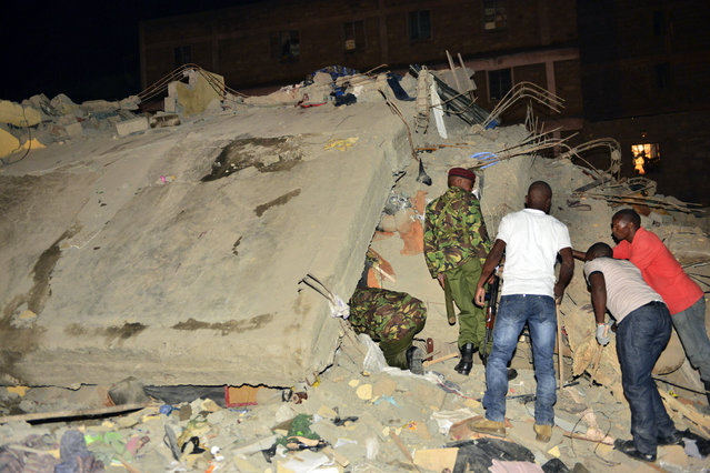 Kenya Para military soldiers and local Kenyans search for survivors of a multi-storey building collapse in the capital Nairobi, Kenya, Sunday, January 4, 2015. (Photo by AP Photo)