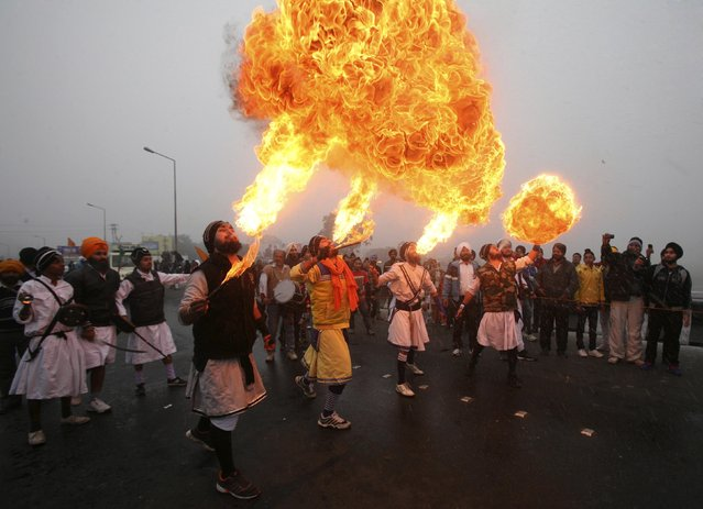 Sikh devotees show off their fire blowing skills during a religious procession ahead of the birth anniversary of Guru Gobind Singh in Jammu January 5, 2014. Guru Gobind Singh was the last and the tenth Guru of the Sikhs. (Photo by Mukesh Gupta/Reuters)