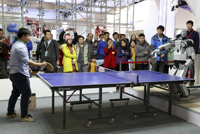 People look on as a robot (R) plays table tennis with a man during an demonstration at the World Robot Conference in Beijing, China, November 23, 2015. The conference, which kicked off in Beijing on Monday, is a three-day event including a forum, an exhibition and a robot contest for youth, Xinhua News Agency reported. (Photo by Reuters/Stringer)